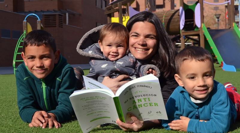 Odile Fernández con sus tres hijos y un ejemplar de su nuevo libro 'Mi revolución anticáncer